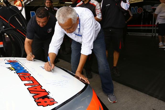 Carol Figueiredo, pai de Nonô Figueiredo assina capô do carro do piloto - Stock Car Curitiba (Foto: Eduardo Petroni / Divulgação)