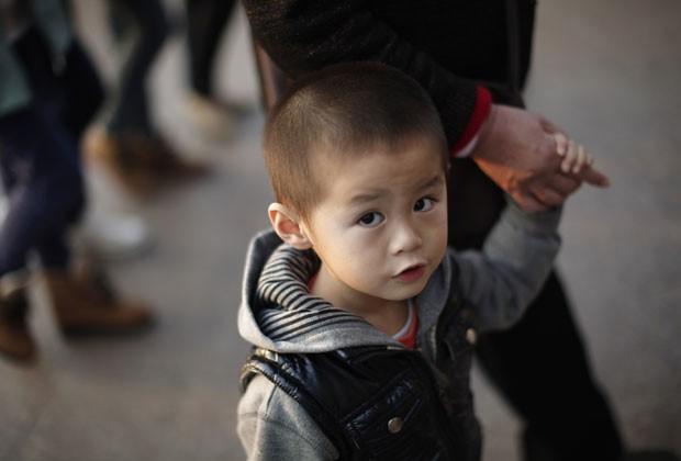 Menino anda com a avó em Xangai, na China, nesta quarta-feira (28). País estuda mudar política do filho único (Foto: Reuters)