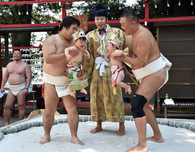 Crianças são seguradas por lutadores de sumô, com objetivo de fazê-las chorar. (Foto: Yoshikazu Tsuno/AFP)
