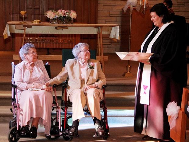 Vivian Boyack (esquerda) e Alice Dubes, durante a cerimônia de seu casamento, celebrada pela reverenda Linda Hunsaker (direita) (Foto: AP Photo/The Quad City Times, Thomas Geyer)