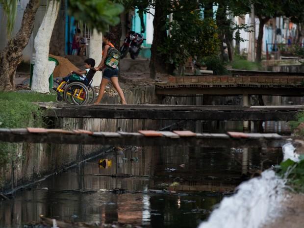 Mãe empurra filho na cadeira de rodas na passarela de madeira no canal da Levada. (Foto: Jonathan Lins/G1)