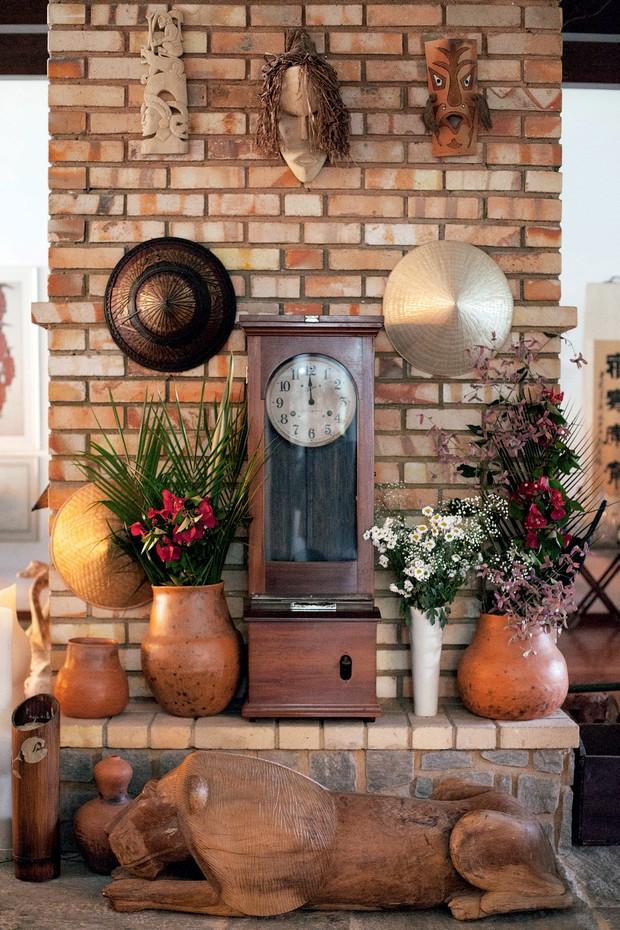 O relógio original dos anos 40, as máscaras africanas e os vasos comprados no interior da Bahia decoram a lareira da sala principal da casa (Foto: Carolina Isabel Novaes)