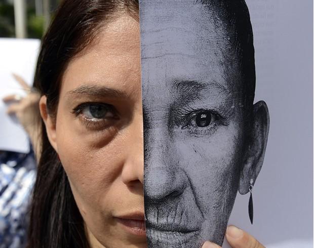 A máscara usada em metade da face presta homenagem à mulher que teve toda a família assassinada. Algumas das envolvidas no protesto tiveram familiares mortos em eventos violentos.  (Foto: AFP PHOTO/JUAN BARRETO)