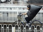 Mulher transforma saco de lixo em capa ao pedalar na chuva na China