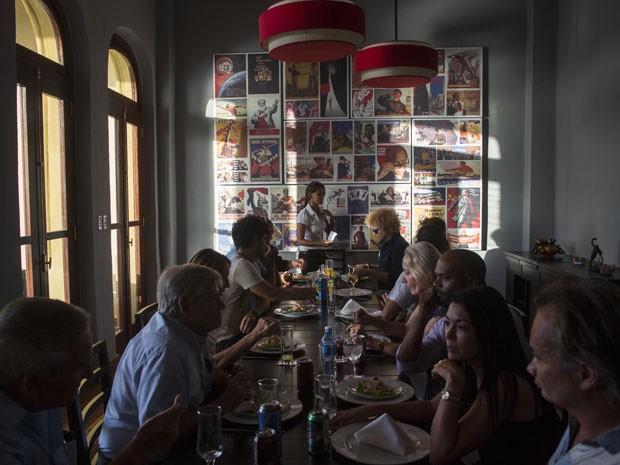 Clientes na mesa comunitária do restaurante (Foto: Ramon Espinosa/AP)