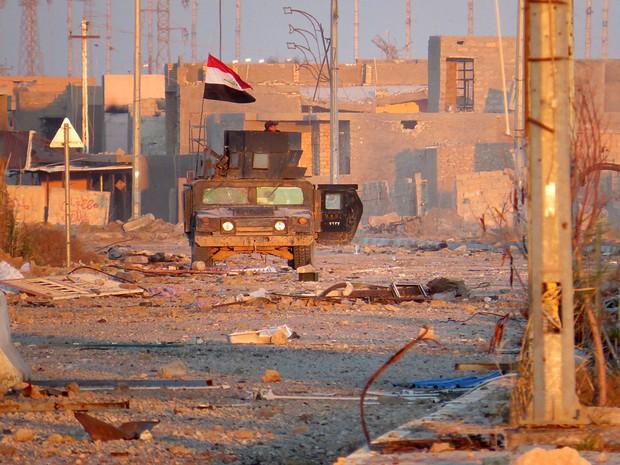 Soldados iraquianos em veículo blindado vigiam rua de Ramadi, onde combatem o grupo Estado Islâmico (Foto: STR/France Presse)