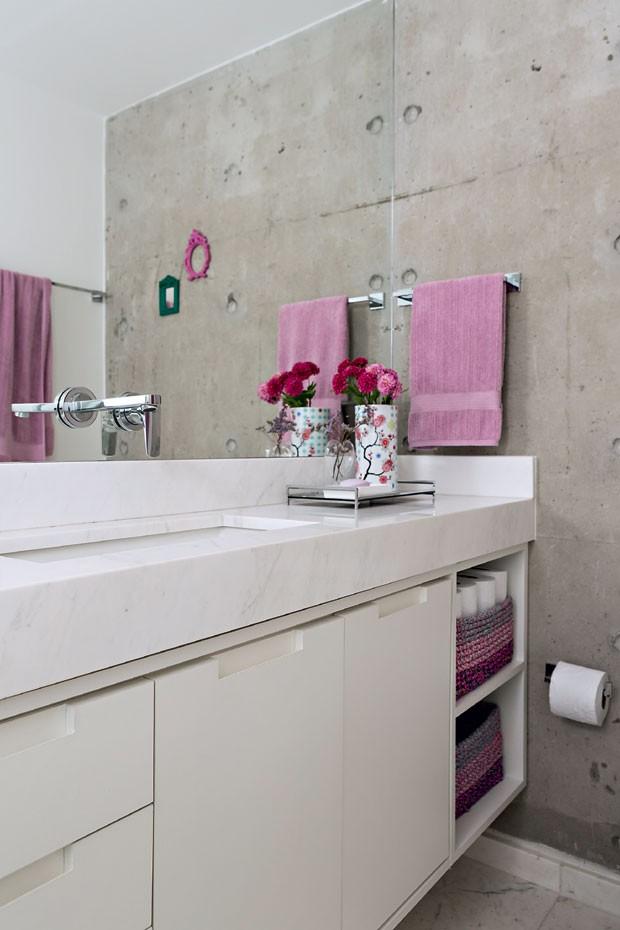 Banheiro | Paredes com acabamento rústico de cimento queimado valorizam a bancada de Corian. Nos nichos, cestos organizadores guardam toalhas (Foto: Edu Castello/Editora Globo)