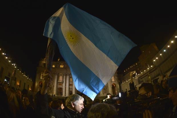 Fiel acena bandeira da Argentina nesta quarta-feira (13) na Praça de São Pedro, no Vaticano (Foto: AP)