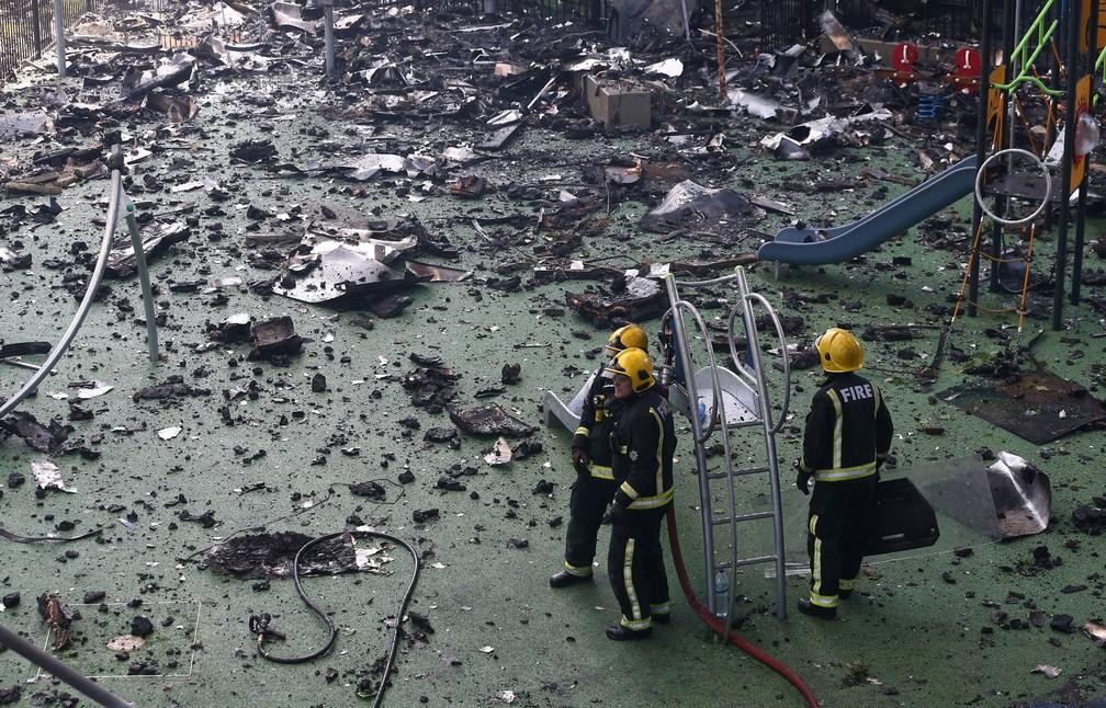 Bombeiros passam por playground coberto de destroços enquanto trabalham no combate ao fogo em uma torre residencial de Londres. na Inglaterra (Foto: Neil Hall/Reuters)
