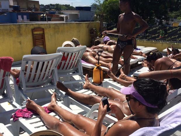 Para afastar o calor, mulheres chamam o 'bombeiro', que borriga água nelas (Foto: Lívia Torres/G1)