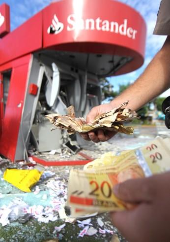 Dinheiro ficou espalhado pelo chão com a explosão (Foto: Alex de Jesus/O Tempo/Folhapress)