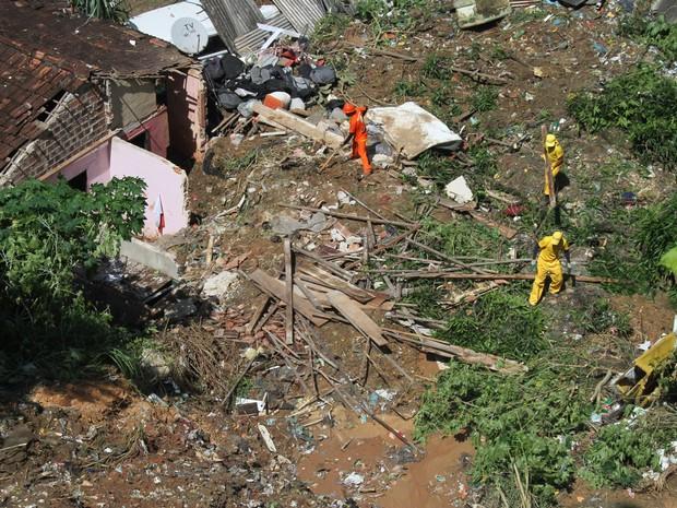 Funcionários trabalham em área onde pai e filho morreram após uma barreira deslizar e atingir a casa onde moravam no bairro da Bomba do Hemetério, na Zona Norte do Recife, durante a madrugada (Foto: Diego Nigro/JC Imagem)