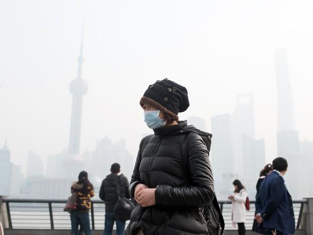 Mulher com máscara no rosto é vista em meio a poluição em Xangai nesta terça-feira (15) (Foto: Johannes Eisele/AFP)