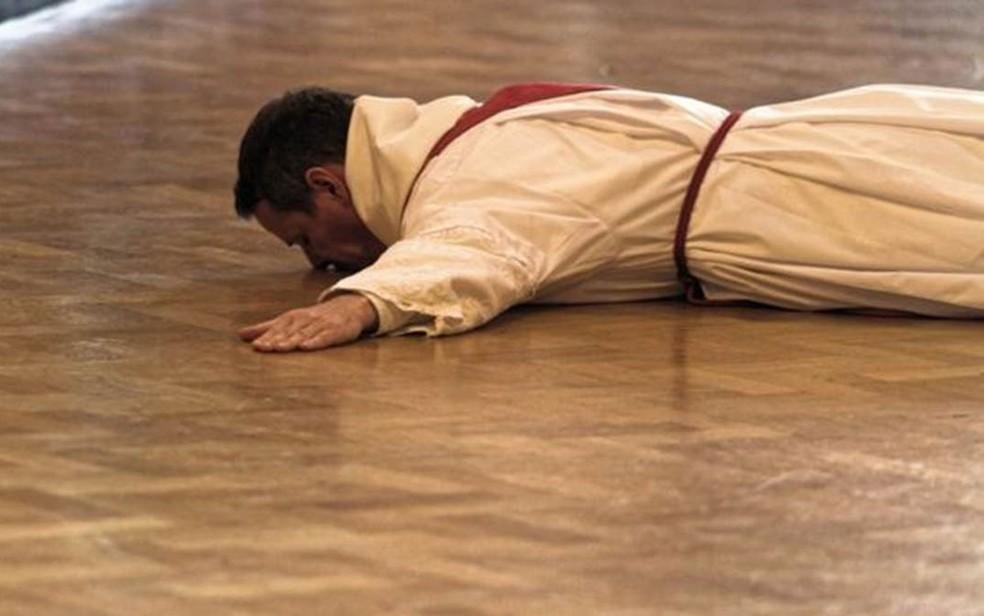 Philip Mulryne beija o chão durante a cerimônia em que foi ordenado como padre, em Dublin (Foto: Philip McShane)