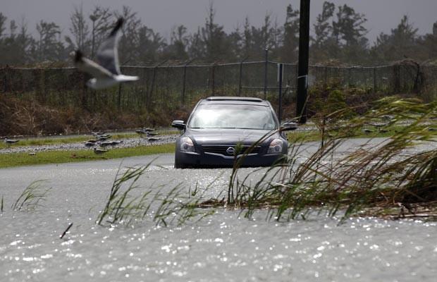Carro passa em área de Venice, Louisiana, já alagada nesta terça-feira (28) por chuva associadas a Isaac (Foto: AP)