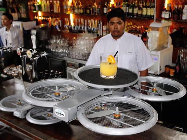 Garçom observa drone em operação (Foto: Reuters)