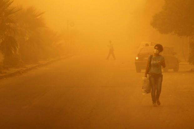 Mulher vestindo máscara anda em tempestade de areia em Homs, na Síria, nesta segunda-feira (7)   (Foto: Reuters/Omar Sanadiki)