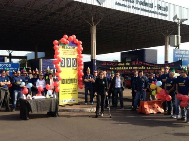 Grupo de servidores cantaram 'Parabéns' e deistribuíram bolo para lembrar os 300 dias de espera pela regulamentação do adicional de fronteira (Foto: Caio Vasques / RPC TV)