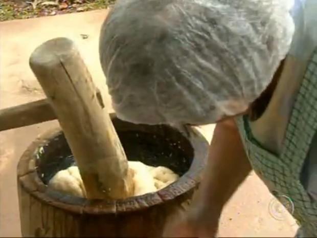 A massa do moti é amassada em pilão durante ritual (Foto: Reprodução/TV Tem)