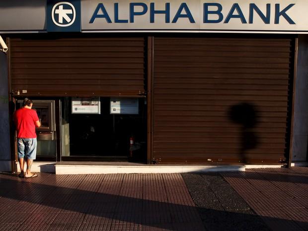 Homem retira dinheiro de um caixa eletrônico em Atenas, Grécia, neste domingo (19) (Foto: REUTERS/Yiannis Kourtoglou)