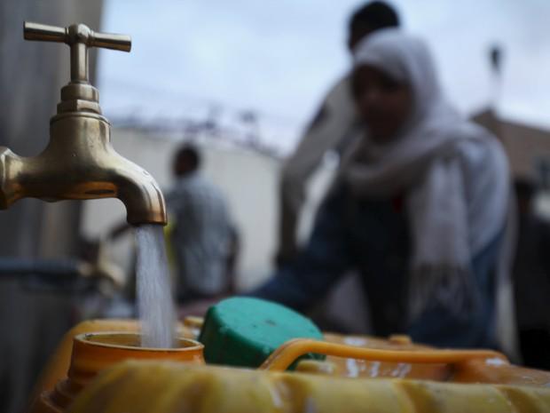 Pessoas enchem recipientes com água em Sana, no Iêmen (Foto: REUTERS/Mohamed al-Sayaghi)