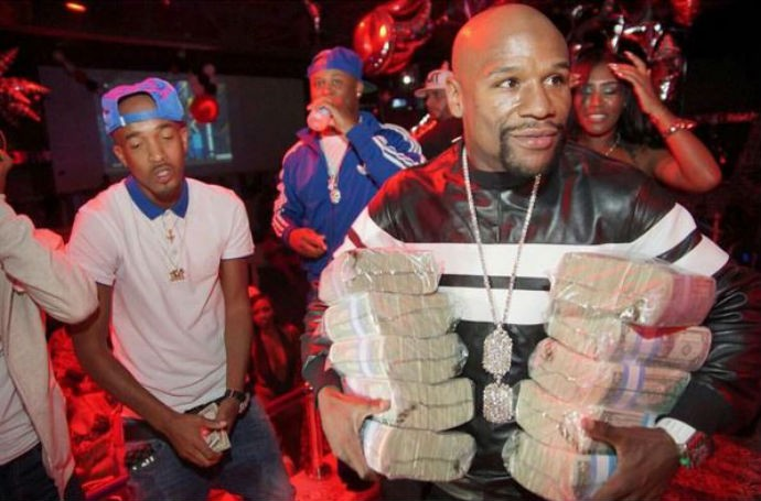 Floyd Mayweather com pacotes de dólares debaixo dos braços (Foto: Reprodução/Instagram)