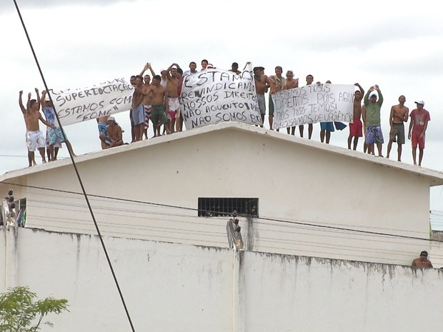 Mais de 700 presos participaram do protesto, e alguns deles subiram nos pavihões para exibirem cartazes e faixas com as reinvindicações (Foto: Reprodução / TV Paraíba)