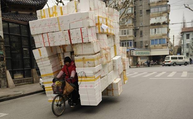 Em 29 de fevereiro deste ano, uma mulher foi flagrada com um triciclo supercarregado com caixas de isopor em uma rua de Xangai, na China. Por conta da quantidade de embalagens, a condutora ficava praticamente escondida no meio, sem visão lateral. (Foto: Peter Parks/AFP)