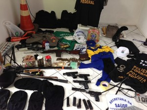 Polícia também encontrou pistolas, um fuzil, toucas ninja, radios de comunicação, além de fardas da polícia e uniformes de órgãos publicos (Foto: Alexandre dos Santos/RBS TV)