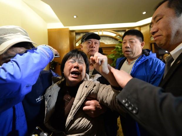 24/3 - Pessoas que perderam parentes no voo da Malaysia Airlines MH370 choram em hotel em Pequim depois de ouvir a notícia de que o avião caiu no Oceano Índico (Foto: Goh ChaiI Hin/AFP)