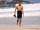 Cauã Reymond caminha na praia após o surfe
