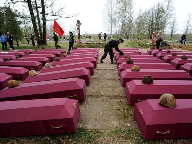 Membro de um grupo de buscas coloca capacetes nos caixões com restos mortais de soldados do Exército Vermelho mortos na II Guerra Mundial, em São Petesburgo, na quinta-feira (7) (Foto: AFP Photo/Olga Maltseva)