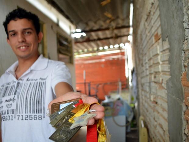O estudante Jesus Cristian exibe coleção de medalhas de olimpíadas estudantis (Foto: Lana Torres / G1)