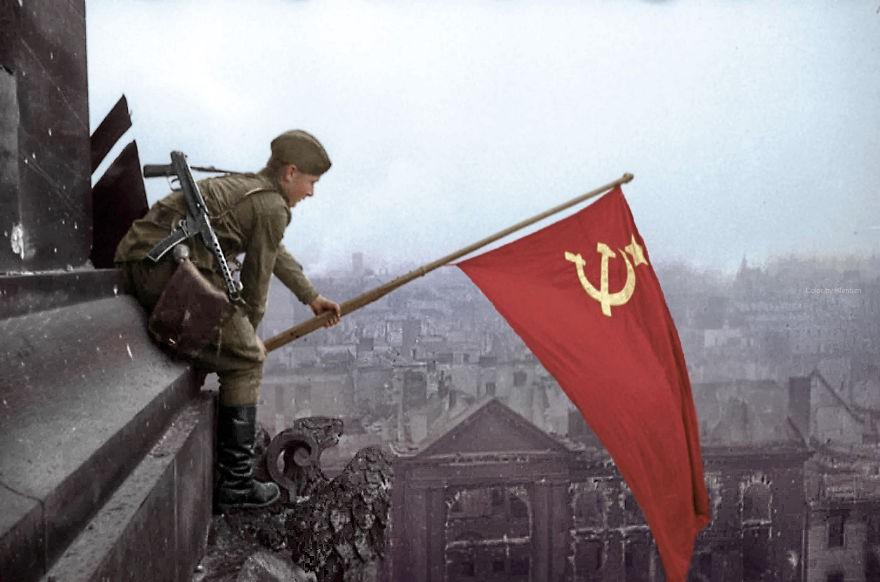Soldado erguendo bandeira soviética em Berlim, no ano de 1945 (Foto: Reprodução)