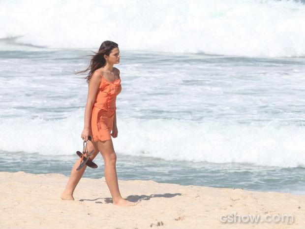 Luiza caminha pensativa na praia (Foto: Pedro Curi/TV Globo)