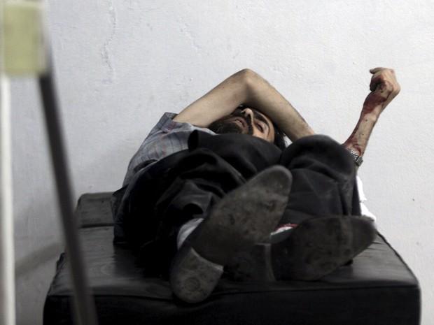 Homem ferido por estilhaços de ataque do governo espera por cuidados médicos em Douma, na Síria (Foto: Mohammed Badra/Reuters)