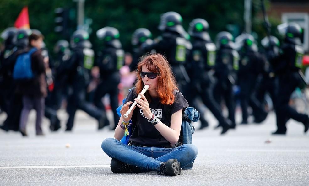 Manifestante toca flauta enquanto polícia passa durante protesto contra a realização do G20, nesta sexta-feira (7)  (Foto: Hannibal Hanschke/ Reuters)