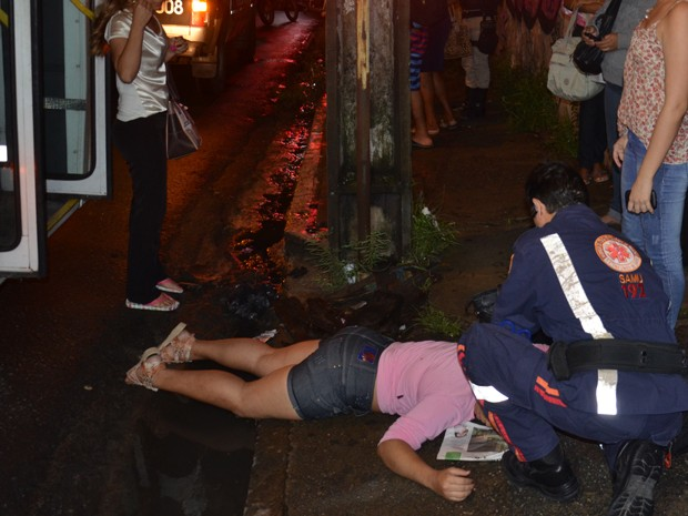 Passageira foi empurrada de cima dos degraus do ônibus pelos assaltantes e bateu com o rosto no chão (Foto: Walter Paparazzo/G1)