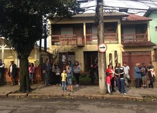 Vizinhos de Patrícia Moreira observam casa que foi incendiada (Foto: Paula Menezes/GloboEsporte.com)