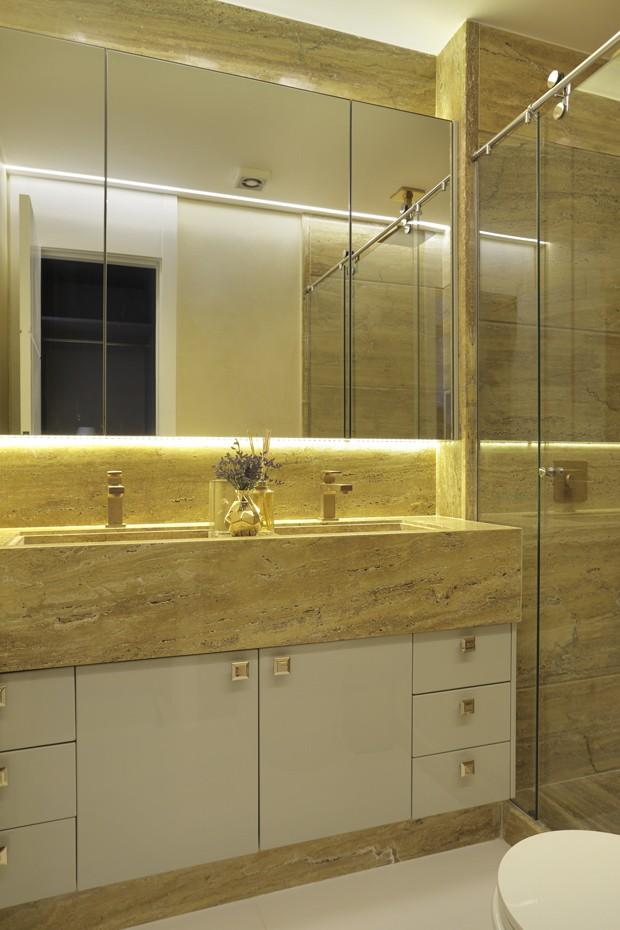 BANHEIRO | Com 6 m², o espaço ganhou bancada de mármore travertino gold, da  Rubini Marmoraria. Metais à venda na Deca. Marcenaria assinada pela Florense. Atente aos puxadores que têm as iniciais do casal (Foto: Denilson Machado/MCA Estudio/Divulgação)
