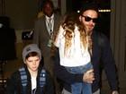 Harper, filha de David Beckham, se esconde de paparazzi no colo do pai