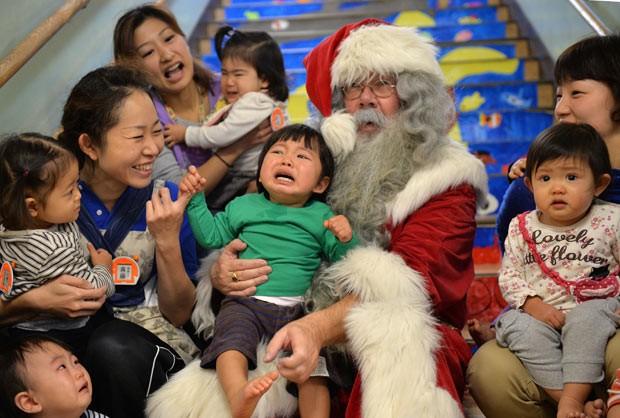 Crianças posam com Papai Noel nesta segunda-feira (9) em Tóquio (Foto: Yoshikazu Tsuno/AFP)