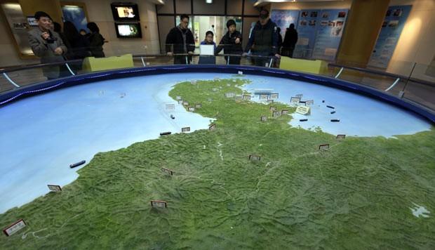 Visitantes olham mapa da Península da Coreia, em posto próximo à cidade fronteiriça de Panmunjon, na Coreia do Sul, neste sábado (30) (Foto: AP)