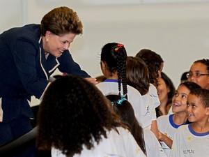 A presidente Dilma Rousseff cumprimenta escolares, durante a cerimônia de lançamento do Pacto Nacional de Alfabetização, no Palácio do Planalto, em Brasília. (Foto: Evaristo Sa/AFP)