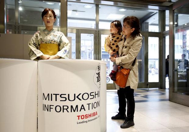 Visitantes olham robô recepcionista em loja em Tóquio nesta segunda-feira (20) (Foto: Issei Kato/Reuters)