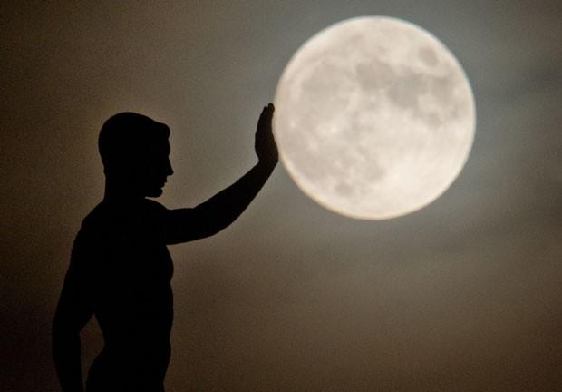 Uma imagem tirada pelo fotógrafo Julian Strantenscgulte dava a impressão de que uma escultura estava segurando a lua. A cena foi registrada pelo fotógrafo alemão em Hanover, na Alemanha, na última segunda-feira (16) (Foto: Julian Stratenschulte/DPA/AFP)