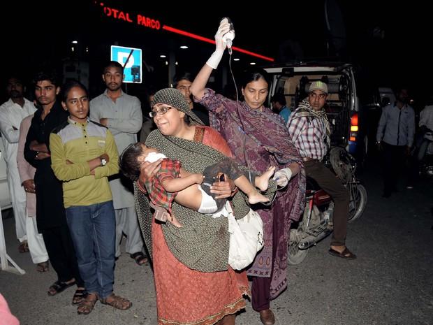 Mulher segura criança que ficou ferida em atentado em parque de Lahore (Foto: Arif Ali/AFP)