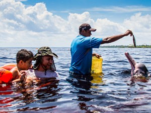 Ajudante de grupo leva criança para brincar com boto (Foto: Diogo Lagroteria/Divulgação)