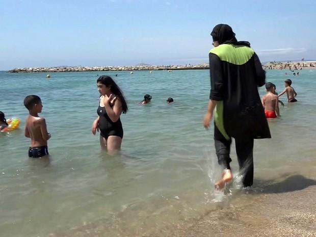 Em foto de arquivo, Nissrine Samali entra no mar usando a veste tradicional islâmica em Marseille, no sul da França  (Foto: AP Photo)