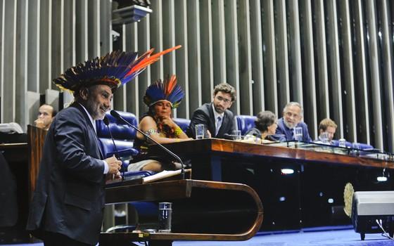 O senador Telmário Mota (PDT-RR) discursa usando um cocar durante sessão no Senado destinada a homenagear os povos indígenas (Foto: Moreira Mariz/Agência Senado)